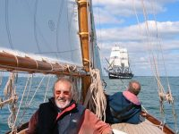 Hal Sisk aboard the newly-restored 1894-built Peggy Bawn in Dublin Bay in 2005, with the square-rigger Jeanie Johnston in the background. Peggy Bawn will be one of the stars of the Classics & Traditional section in the Volvo Dun Laoghaire Regatta 2017, celebrating the Bicentenary of the harbour | Photo: W M Nixon